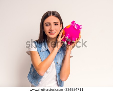 Portrait of cheerful girl teenager holding a pink pig on a white background - stock photo
