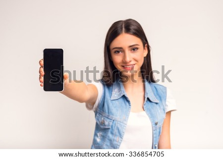 Portrait of cheerful girl teenager using the phone on a white background - stock photo