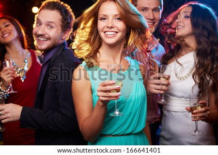 Portrait of cheerful girl with champagne flute dancing at party on background of her friends