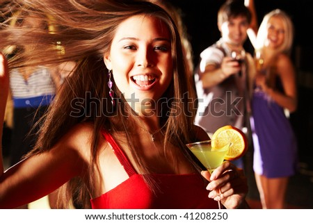Portrait of cheerful girl with cocktail in hand laughing