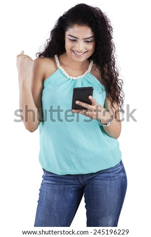 Portrait of cheerful girl with long curly hair reading message on the mobile phone - stock photo