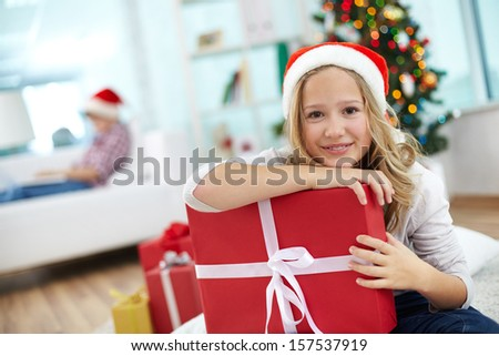 Portrait of cheerful girl with red giftbox looking at camera on Christmas evening - stock photo