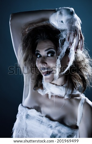 Portrait of cheerful girl-zombie posing at camera - stock photo