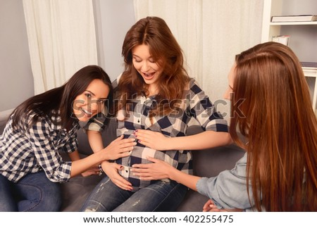 Portrait of cheerful girls touching tummy of their pregnant sister - stock photo