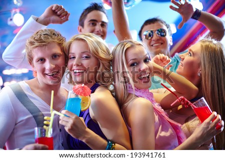 Portrait of cheerful girls with cocktails at party with happy friends near by - stock photo