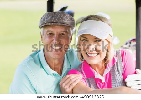 Portrait of cheerful golfer couple sitting in golf buggy - stock photo
