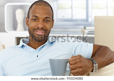 Portrait of cheerful handsome black man sitting at home with mug handheld, drinking tea, smiling at camera.?