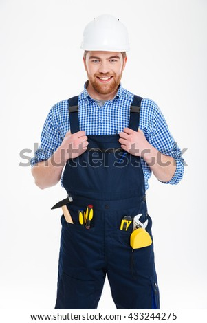 Portrait of cheerful handsome young builder in helmet standing and smiling - stock photo