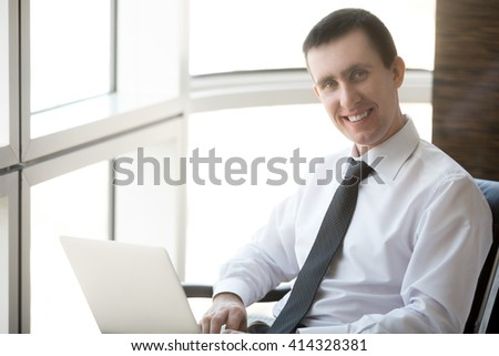 Portrait of cheerful handsome young business man sitting in his office and working on laptop computer. Happy Caucasian businessperson looking at camera with confident friendly smile - stock photo