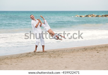 Portrait of cheerful happy father and son on background of sea, Spain