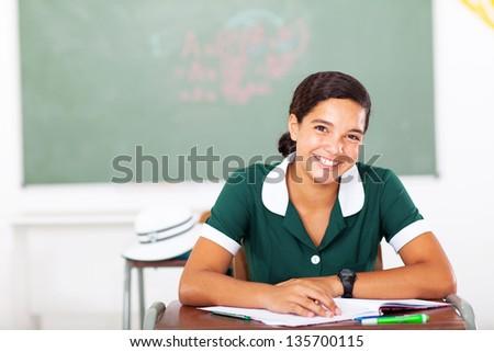 portrait of cheerful high school girl sitting in classroom - stock photo