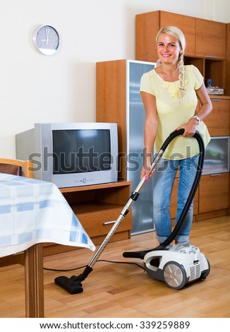 Portrait of cheerful housewife vacuuming at home interior - stock photo