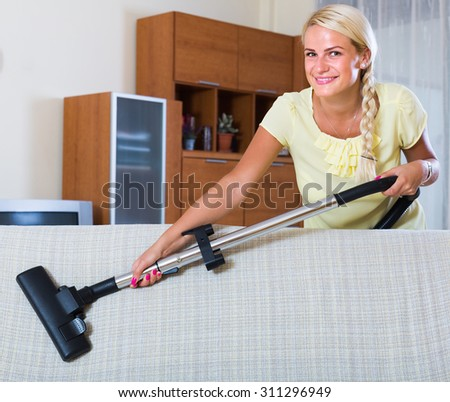 Portrait of cheerful housewife vacuuming in living room at home - stock photo