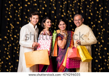 portrait of cheerful indian family with shopping bags in traditional wear in diwali isolated over black background