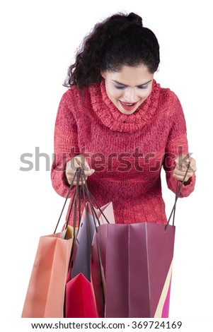 Portrait of cheerful indian woman opens shopping bags in the studio while wearing winter clothes - stock photo
