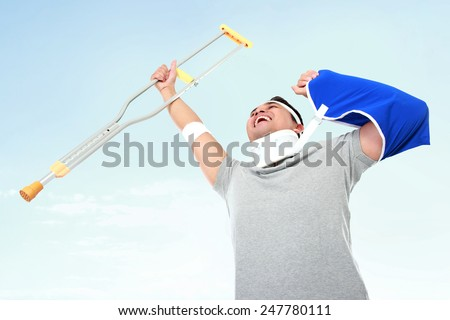 portrait of cheerful injured young man hold up the crutch - stock photo