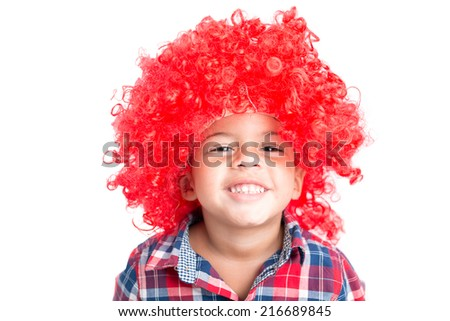 Portrait of cheerful little boy in a curly red wig - stock photo