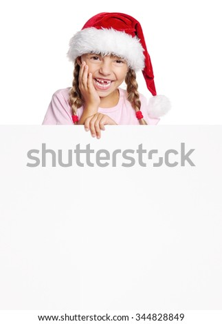 Portrait of cheerful little girl in Santa hat with white blank - stock photo