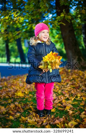 portrait of cheerful little girl with bouquet of maple leaves in autumn park