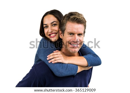 Portrait of cheerful man carrying girlfriend on back against white background