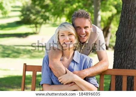 Portrait of cheerful man embracing woman from behind in park - stock photo