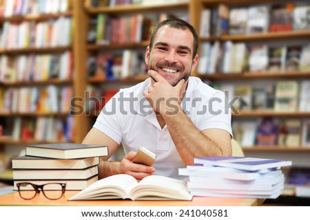 Portrait of cheerful man in a polo shirt in a bookstore - stock photo