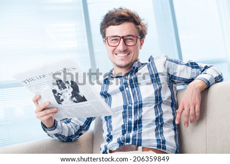 Portrait of cheerful man reading daily newspaper - stock photo
