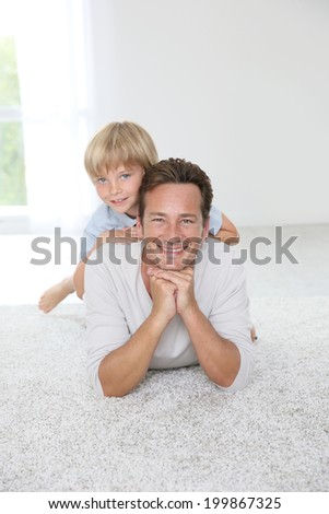 Portrait of cheerful man with 7-year-old son - stock photo