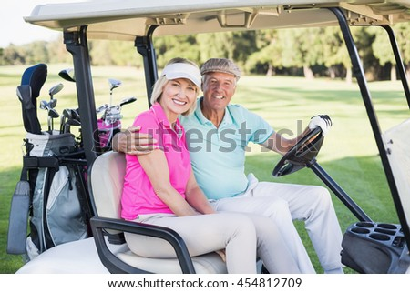 Portrait of cheerful mature couple sitting in golf buggy - stock photo