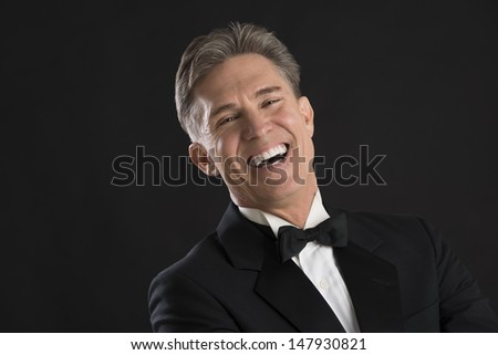 Portrait of cheerful mature man in tuxedo laughing against black background - stock photo