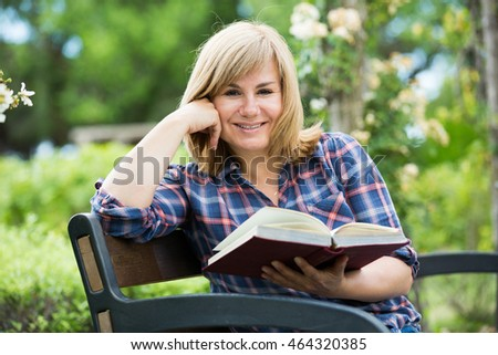Portrait of cheerful mature woman sitting on bench and reading book outdoors in garden