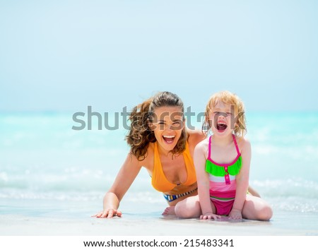 Portrait of cheerful mother and baby girl on sea shore - stock photo