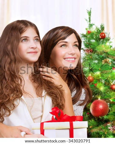 Portrait of cheerful mother and daughter with wonder looking up, celebrating holidays near beautiful decorated Christmas tree, with pleasure receiving festive gift box - stock photo