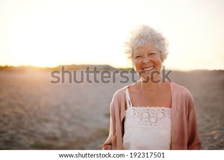 Portrait of cheerful old woman standing on the beach. Smiling senior caucasian female smiling outdoors. - stock photo