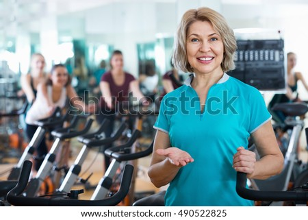 Portrait of cheerful positive mature blonde smiling in exercise bikes class