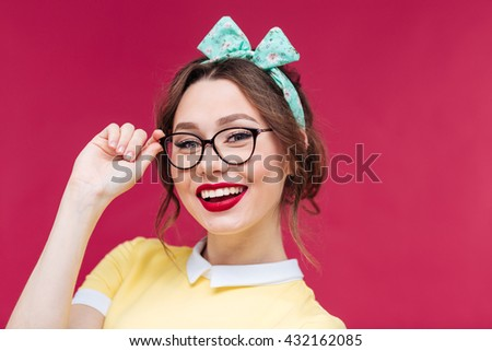 Portrait of cheerful pretty young woman in glasses over pink background - stock photo