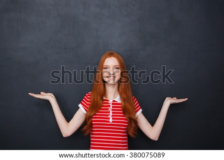 Portrait of cheerful redhead young woman holding copyspace on both palms over chalkboard background - stock photo