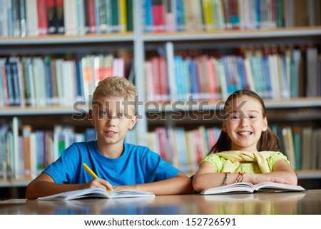 Portrait of cheerful schoolchildren looking at camera while sitting in library - stock photo