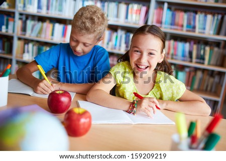 Portrait of cheerful schoolgirl looking at camera while sitting in library with her classmate near by - stock photo