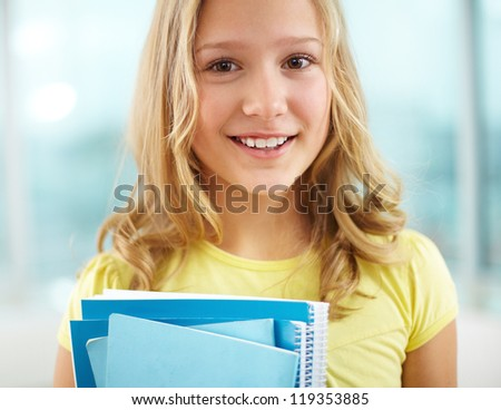 Portrait of cheerful schoolgirl with copybooks looking at camera - stock photo