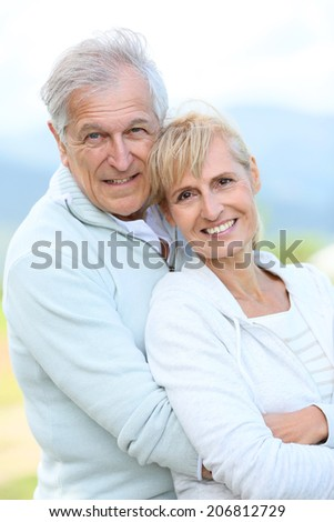 Portrait of cheerful senior couple embracing each other - stock photo