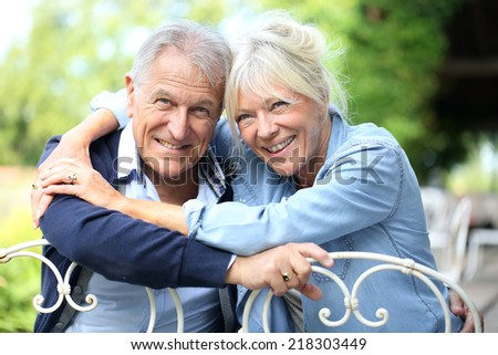 Portrait of cheerful senior couple in home garden - stock photo