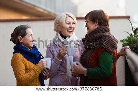 Portrait of cheerful senior female friends drinking coffee at patio. Focus on blonde - stock photo