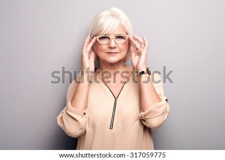Portrait of cheerful senior woman wearing eyeglasses, looking at camera. Lady with grey hair. Studio shot. - stock photo