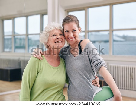 Portrait of cheerful senior woman with her personal trainer at gym. Two women standing together smiling at camera at health club. - stock photo