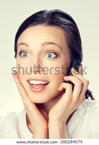 Portrait of cheerful smiling brunette businesswoman with cellphone - stock photo