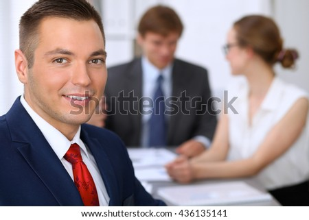 Portrait of cheerful smiling business man  at meeting. - stock photo
