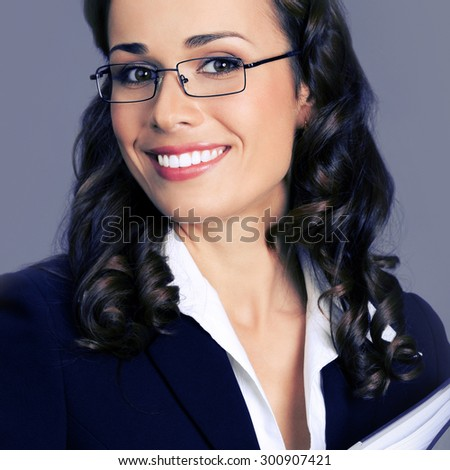 Portrait of cheerful smiling businesswoman in glasses, posing at studio, over violet background - stock photo