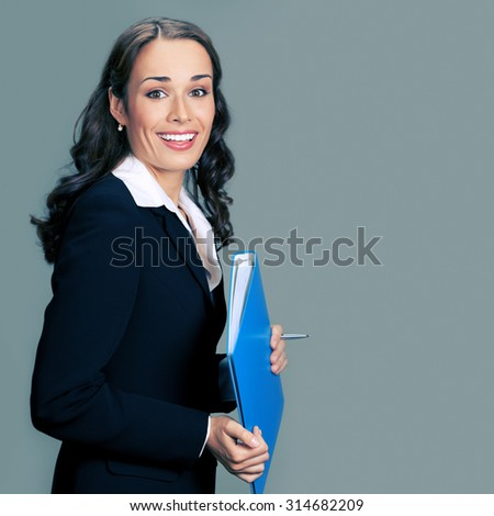 Portrait of cheerful smiling businesswoman in glasses, with blue folder, with blank copyspace area for slogan or text - stock photo