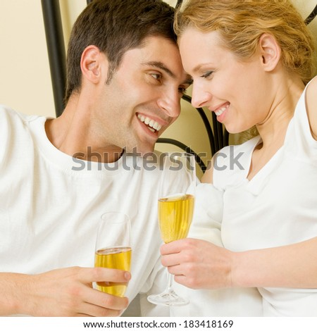 Portrait of cheerful smiling couple with champagne, indoors - stock photo